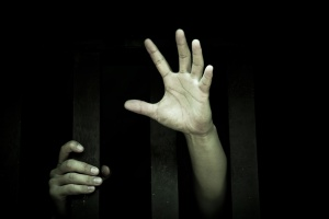 Human hand stretch out from prison bars