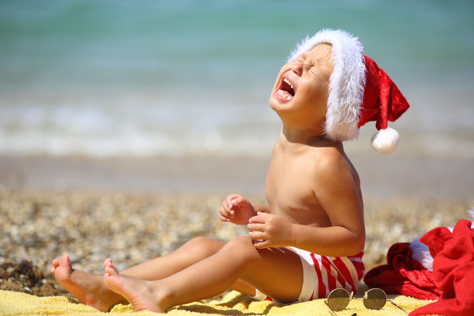 toddler Santa Claus resting on the sea in summer